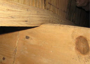 A failing girder showing signs of compression damage in a Ontario home